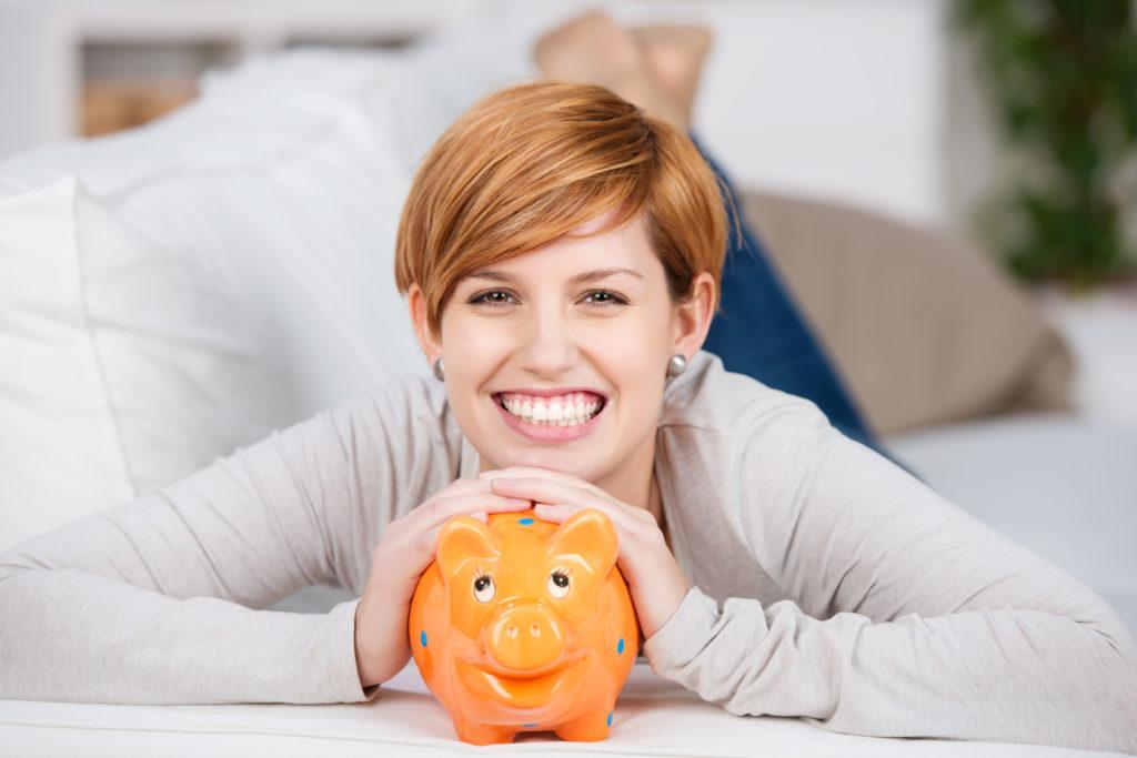 Erfolgreiche Vorsorge: lachende junge Frau mit Sparschwein