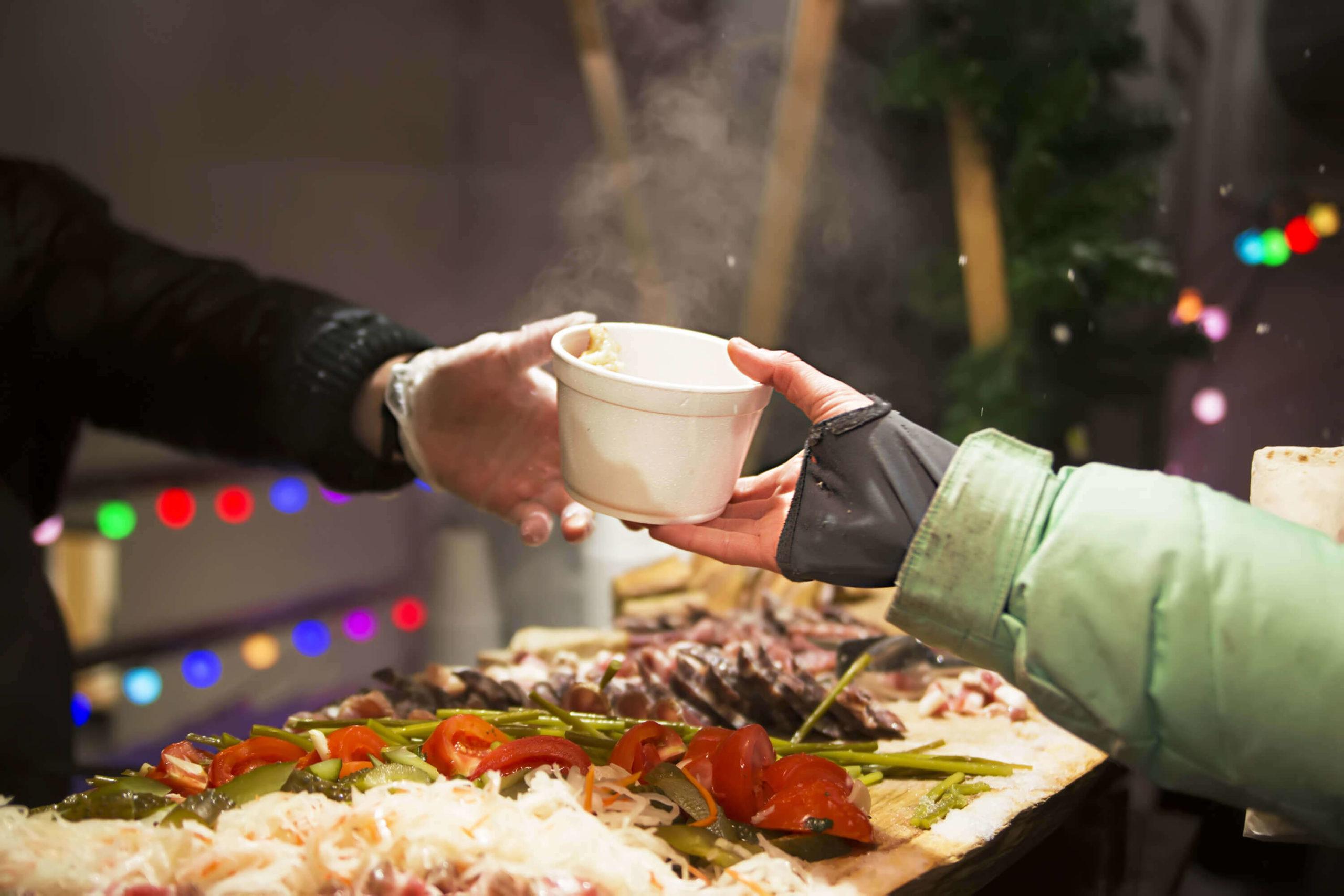 Hand überreicht Becher bei Weihnachtsfeier mit obdachlosen Menschen